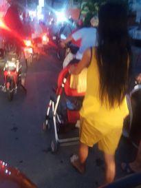 Người phụ nữ đẩy xe nôi em bé giữa phố tắc đường đầy khói xe