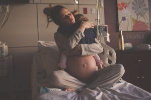 Đằng sau bức ảnh bà mẹ ôm con gái vào lòng trước khi sinh con thứ